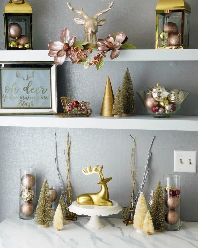 Blush pink and gold holiday decor. Christmas bulbs decorating, lanterns and bottle brush trees.