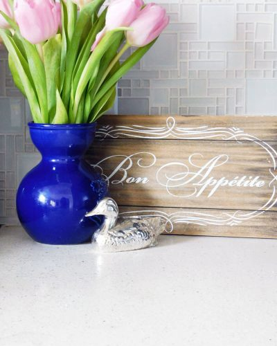 white glass tile, blue vase with pink tulips. rustic bon appetite sign and small silver duck