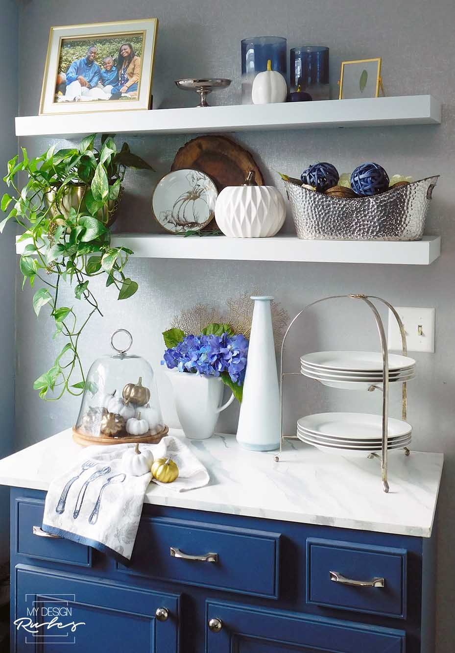 blue buffet and floating shelves decorated for fall